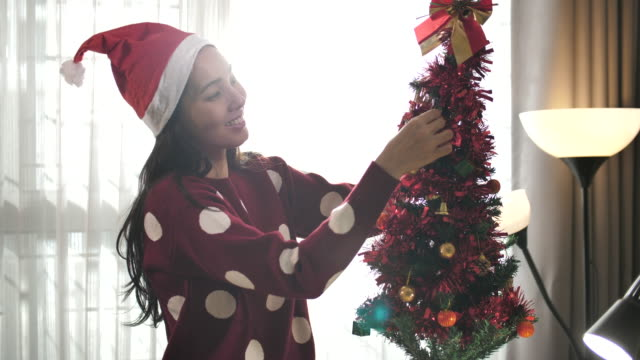woman decorating the christmas ball on the christmas tree at home - advent stock videos & royalty-free footage