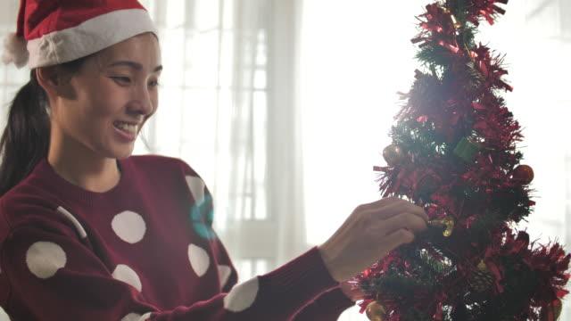 ボールの装飾でクリスマスツリーを飾る女性 - ティンセル点の映像素材/bロール