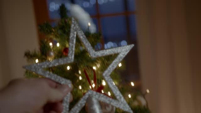 stockvideo's en b-roll-footage met vrouw die bovenkant van kerstboom met ster thuis verfraaien - star shape
