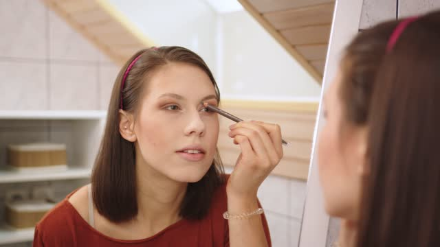 woman defining her eyebrows using a brown eyebrow pencil - caucasian appearance stock videos & royalty-free footage