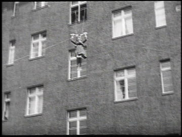 1930 montgage woman descending on ropes and pulley out window from tall building for fire rescue technique, may 14, 1930 / berlin, germany  - 1930 bildbanksvideor och videomaterial från bakom kulisserna