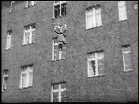 1930 montgage woman descending on ropes and pulley out window from tall building for fire rescue technique, may 14, 1930 / berlin, germany  - 1930 stock-videos und b-roll-filmmaterial