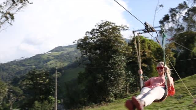 Woman descends zip line in swing seat, mountain meadow