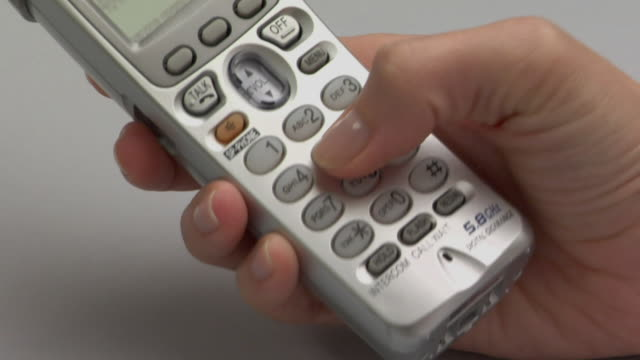 CU, Woman dialing number on cordless phone, close-up of hand