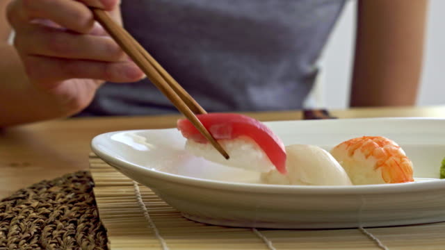 woman dipping sushi in a soy sauce - wasabi stock videos and b-roll footage