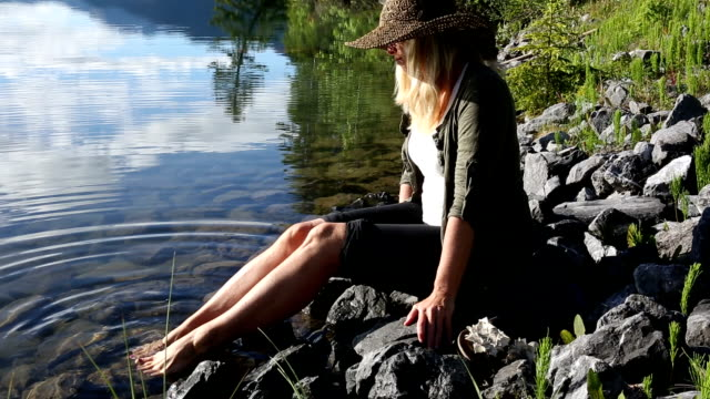 woman dips toes into clear mountain lake - toe stock videos & royalty-free footage