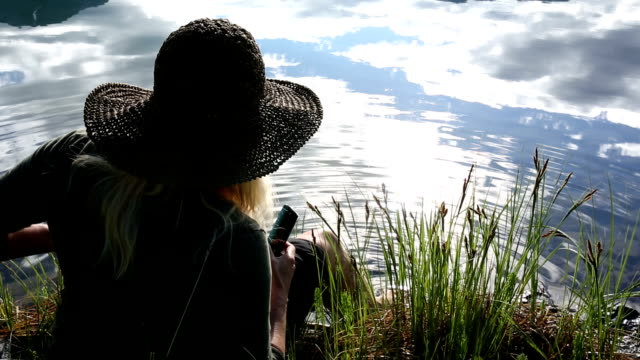 Woman dips toes into clear mountain lake