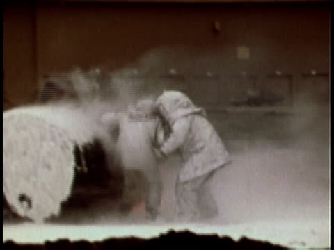 1979 montage woman directing firefighting team hosing down land with water and fire extinguishers in training exercise / united states - fire extinguisher stock videos & royalty-free footage