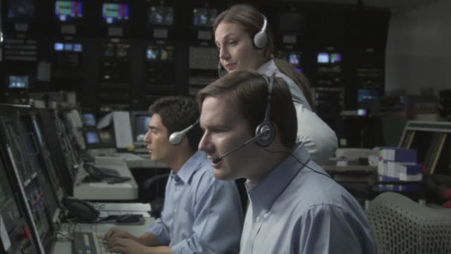 ms woman directing two businessmen in television studio control room / culver city, california, usa - annoying colleague stock videos & royalty-free footage