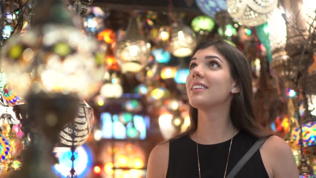 stockvideo's en b-roll-footage met vrouw ontdekt verlichte kroonluchters in een bazar - grote bazaar van istanboel istanboel