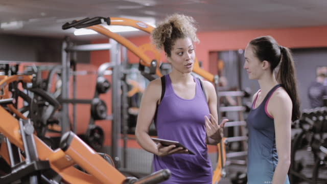 woman discussing workout progress with fitness instructor - females stock videos & royalty-free footage
