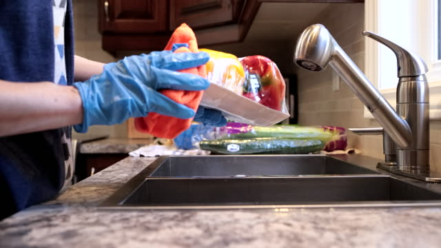 woman disinfecting groceries, fruits and vegetables during covid-19 crisis at home - glove stock videos & royalty-free footage