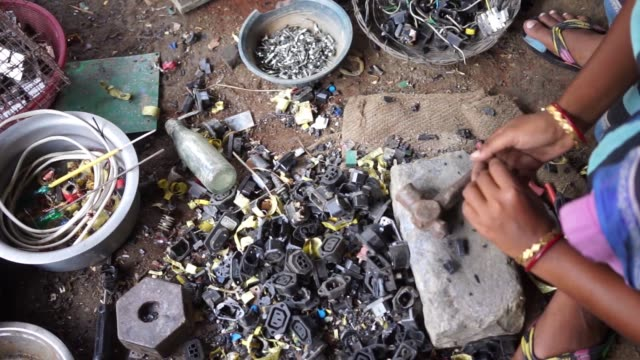 a woman dismantles computer peripherals while sitting next to bags of electronic waste at a house in sangrampur village computer cables and other... - e waste stock videos & royalty-free footage