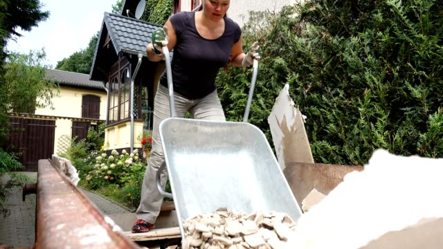 woman disposing house rubbish. - wheelbarrow stock videos and b-roll footage