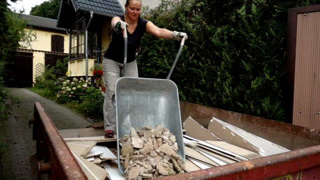 Woman disposing house rubbish.