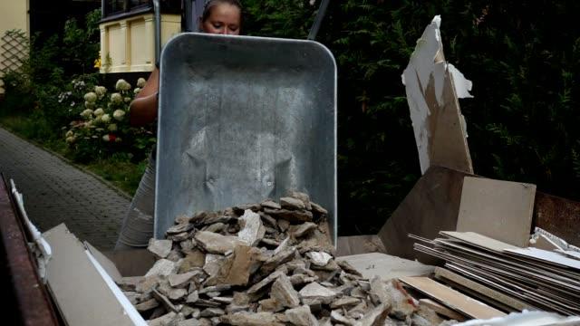 Woman disposing house rubbish.