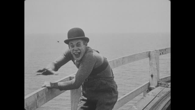 1918 woman dives from roller coaster to escape pursuing villain before panicked men (buster keaton & fatty arbuckle) attempt to rescue her from water - schurke stock-videos und b-roll-filmmaterial