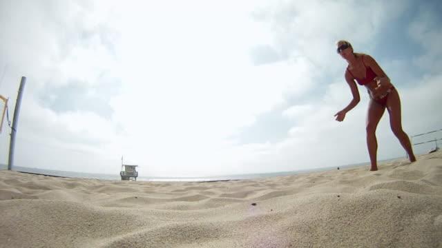 ms ts slo mo woman diving for beach volleyball / redondo beach, california, united states - cabina del guardaspiaggia video stock e b–roll