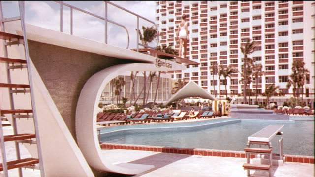 1958 montage ws woman diving from spring board into hotel americana outdoor swimming pool, underwater view of woman swimming towards camera / miami beach, florida, usa / audio - 室外プール点の映像素材/bロール