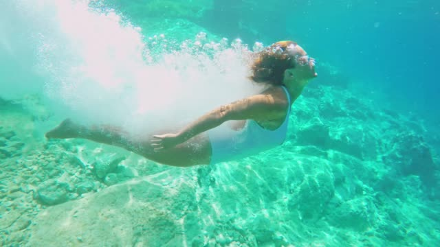 ms woman diving into sunny blue ocean - surfacing stock videos & royalty-free footage