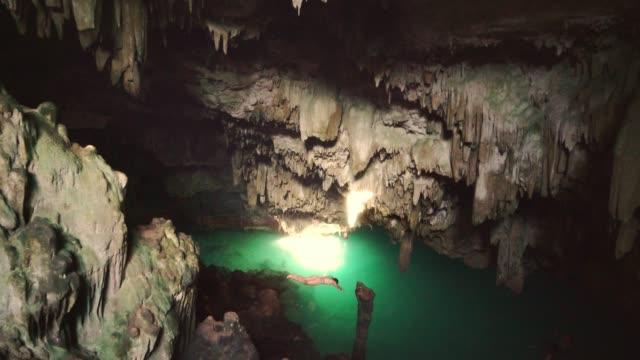 フローレス島の洞窟で水に飛び込む女性 - アゾレス諸島点の映像素材/bロール