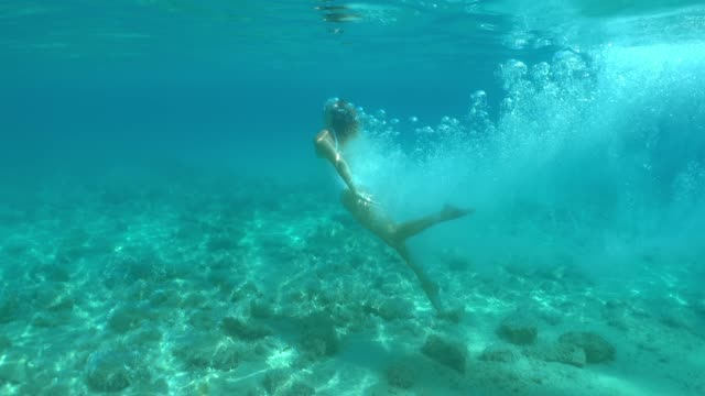 ms woman diving underwater in sunny blue ocean - surfacing stock videos & royalty-free footage