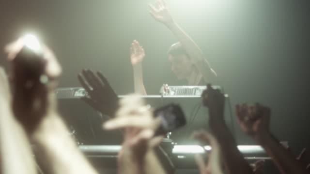 SLO MO woman DJ in crowded nightclub, crowd waving hands in air / New York, New York