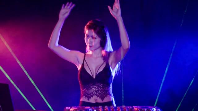 woman DJ jockey mixing music at night club