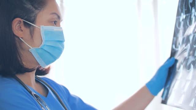 vídeos y material grabado en eventos de stock de mujer doctora analizando la película de rayos x en su espacio de trabajo en el hospital - letra x