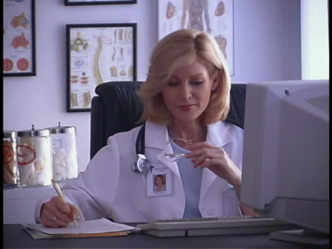 woman doctor at desk - only mid adult women stock videos & royalty-free footage