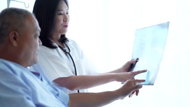 vídeos y material grabado en eventos de stock de el médico de la mujer revisa la radiografía de la película y analiza una enfermedad del progreso fo al concepto paciente, sano. - articulación humana