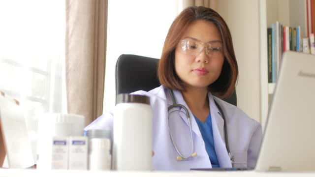 Woman doctor checking Medicine and filling on chart with laptop