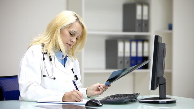 vídeos de stock, filmes e b-roll de mulher médico examinando a imagem de raio-x - analisando