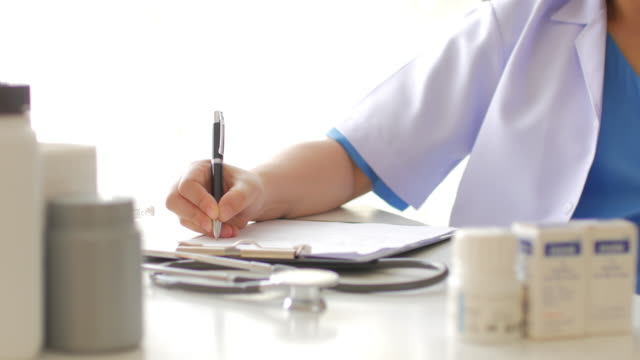 Woman doctor filling on clipboard at her desk