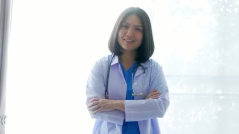 woman doctor in uniform suit standing on white room background - female doctor stock videos & royalty-free footage