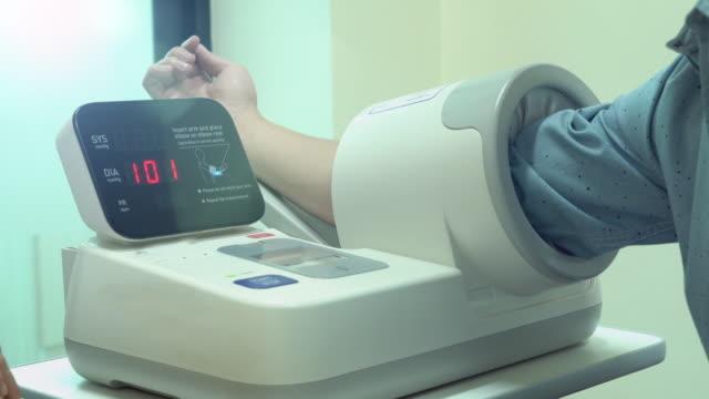 woman doctor measuring the male patients blood pressure - blood pressure gauge stock videos & royalty-free footage