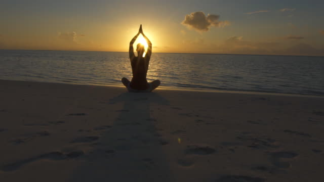a woman does a seated yoga pose on the beach with hands up at sunset. - slow motion - kvinnor i 30 årsåldern bildbanksvideor och videomaterial från bakom kulisserna