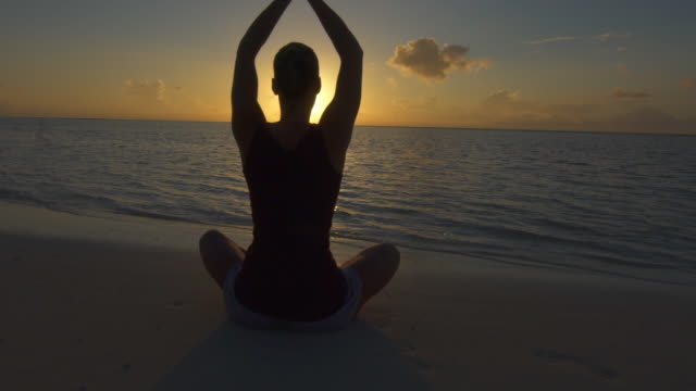 a woman does a seated yoga pose on the beach with hands up at sunset. - slow motion - prayer pose yoga stock videos & royalty-free footage