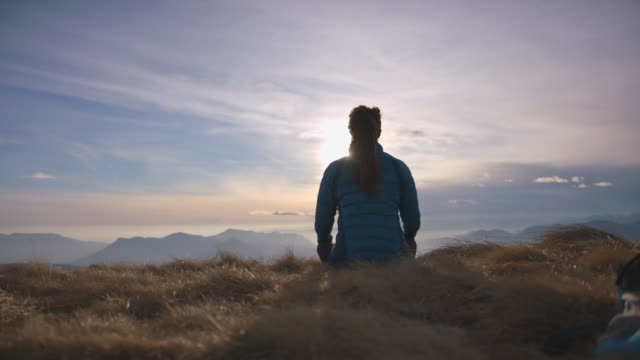 woman does yoga, mediates, practices mindfulness on top of mountain - serene people stock videos & royalty-free footage