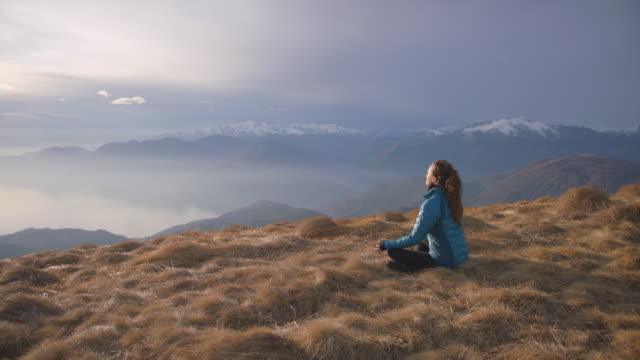 woman does yoga, mediates, practices mindfulness on top of mountain - top garment stock videos & royalty-free footage
