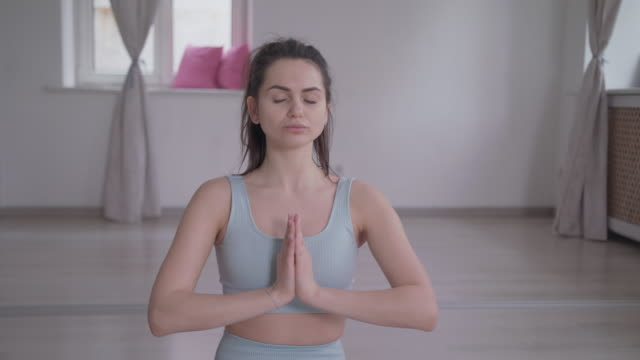a woman does yoga stretching lotus poses prayer position in a dance studio. - lotus position stock videos & royalty-free footage