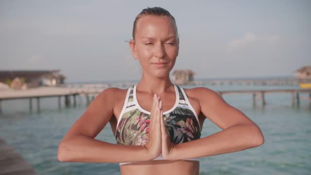 vídeos y material grabado en eventos de stock de a woman does yoga stretching lotus poses prayer position on a dock of a tropical island. - gratitud