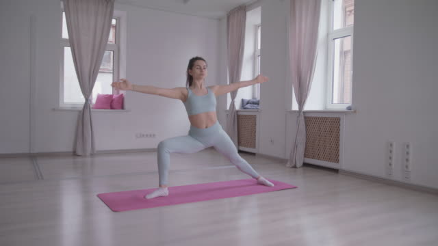 a woman does yoga stretching triangle poses in a dance studio. - yoga stock-videos und b-roll-filmmaterial