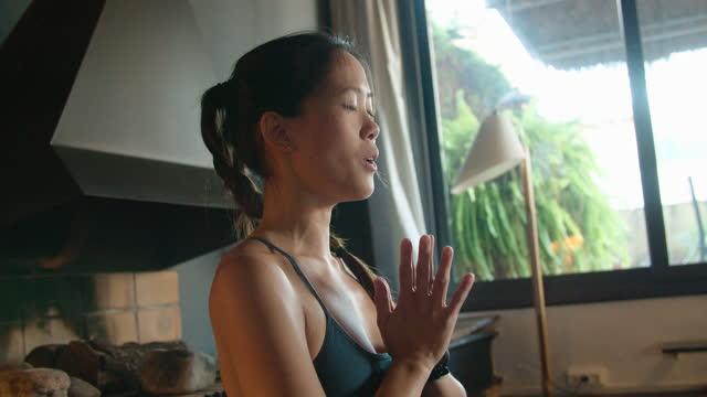 vídeos y material grabado en eventos de stock de woman doing a meditation exercise. hands together in prayer pose saying om sound - zen