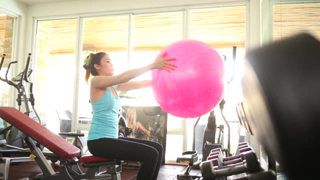 Vrouw doen een kant stretching oefening met behulp van fitball in fitnessstudio - kleur ingedeeld beeldmateriaal