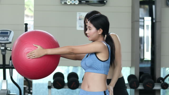 woman doing a side stretching exercise using fitball in fitness studio - pallone per fitness video stock e b–roll