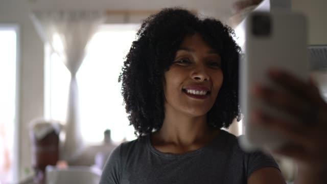 vidéos et rushes de femme faisant un appel vidéo à la maison utilisant le téléphone portable - 30 34 ans