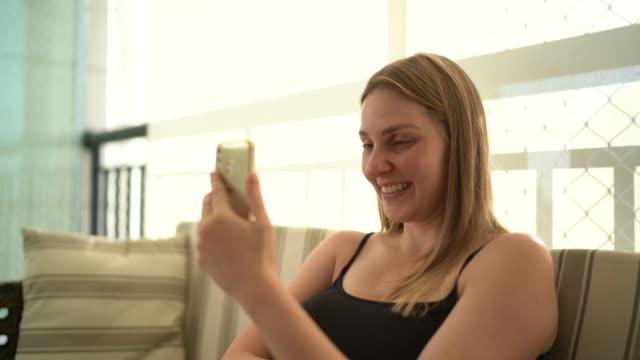 vídeos de stock, filmes e b-roll de mulher fazendo uma chamada de vídeo no celular em casa - sentir a falta emoção