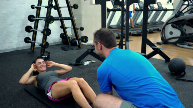 woman doing abs and when she finishes coach gives her a high five - allenatore video stock e b–roll