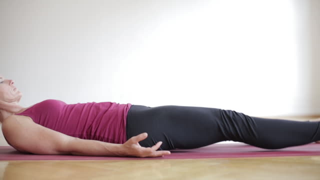 woman doing ashtanga yoga - lying on back stock videos & royalty-free footage